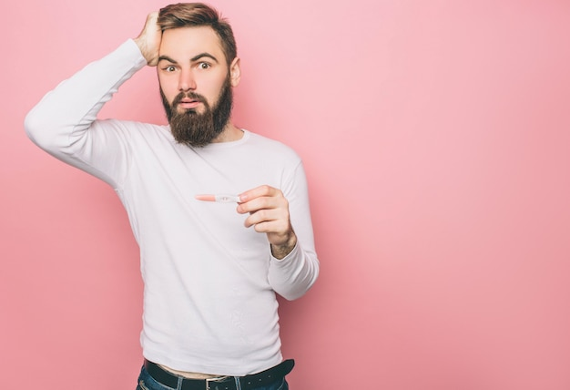 Un homme étonné a un test de grossesse dans ses mains