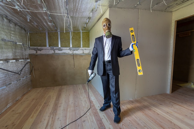 Homme étrange en costume d'homme d'affaires et masque de protection contre les gaz à l'intérieur d'une pièce en rénovation