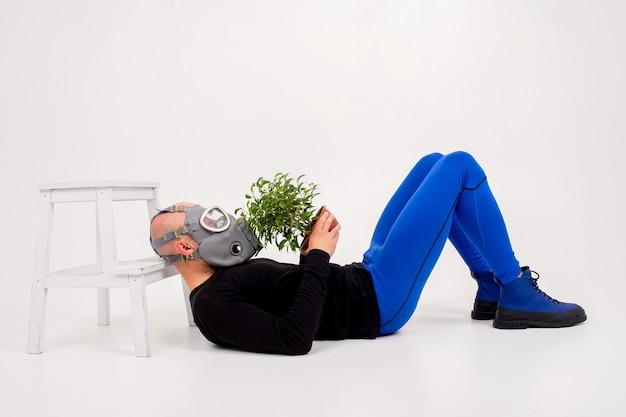 Homme étrange drôle dans un respirateur couché avec une fleur dans le pot