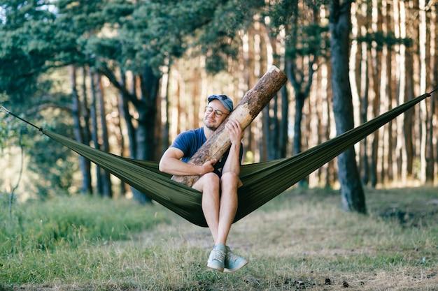 Homme étrange étrange étrange étrange. outlandish drôle fou fou insensé dormir dans un hamac avec un énorme journal en bois à la nature parmi les arbres.
