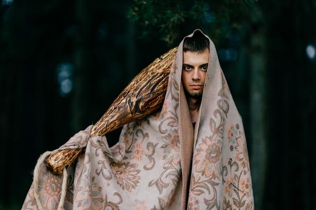 Homme étrange recouvert d'une couverture debout avec un bâton en bois à la main dans la forêt