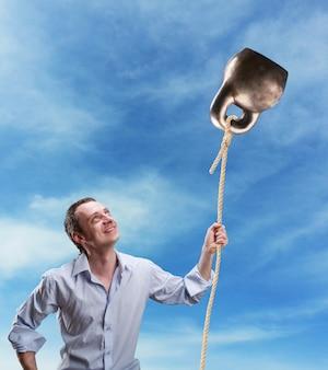 L'homme étrange tient un kettlebell comme ballon contre le ciel