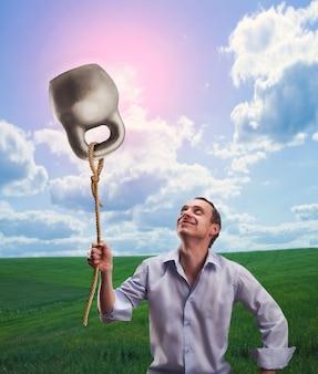 L'homme étrange tient un kettlebell comme ballon sur un pré