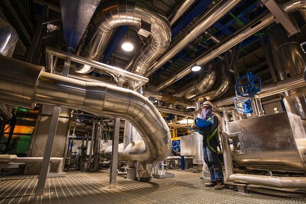 Homme d'être un travailleur inspection visuelle à l'intérieur de la vanne de la salle de commande et des centrales électriques de pipeline