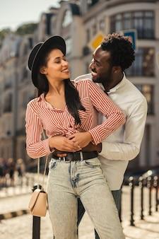 Homme étreignant doucement sa petite amie. jeune femme tournant la tête et lui souriant