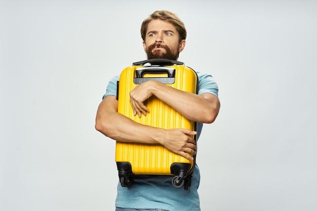Homme étreignant valise jaune voyage et tourisme tshirt fond clair