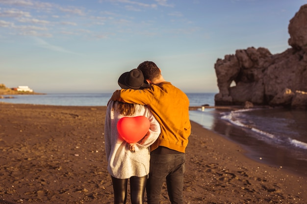 Homme, étreindre, femme, à, ballon coeur rouge, sur, bord mer
