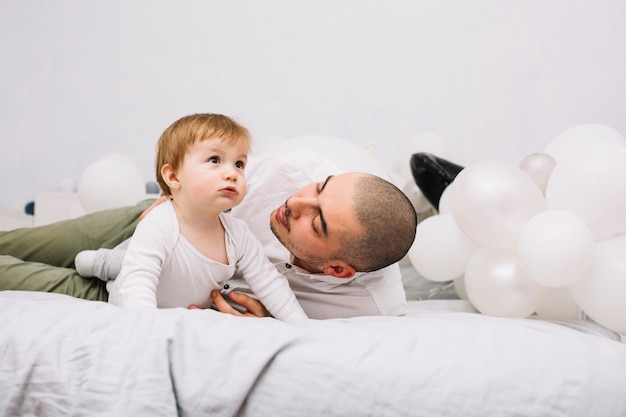 Homme, étreindre, petit bébé, sur, lit, près, ballons