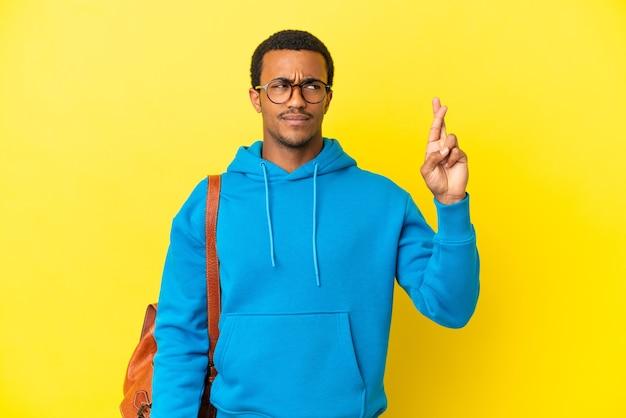 Homme étudiant afro-américain sur fond jaune isolé avec les doigts croisés et souhaitant le meilleur