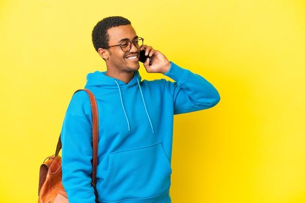 Homme étudiant afro-américain sur fond jaune isolé en gardant une conversation avec le téléphone mobile