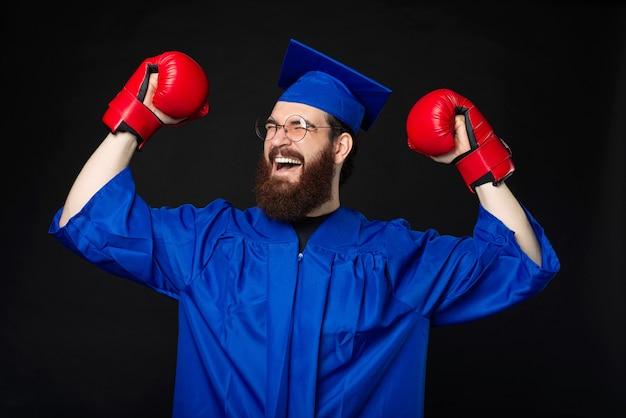 Homme étudiant barbu excité en célibataire bleu célébrant avec des gants de boxe