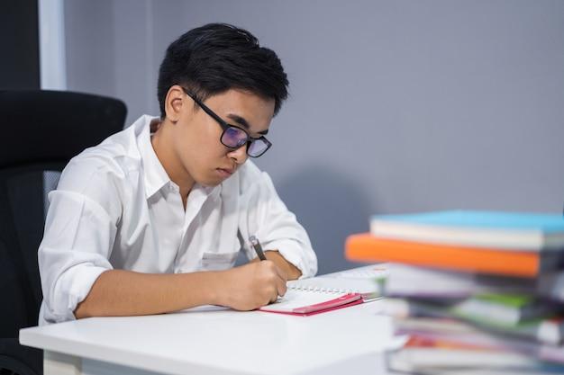 Homme étudiant et écrivant sur ordinateur portable