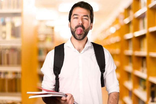Homme étudiant faisant une blague sur une bibliothèque défocalisée