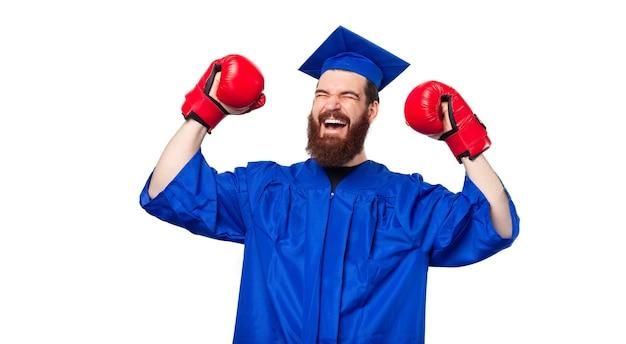 Homme étudiant gai célébrant avec diplôme avec des gants de boxe