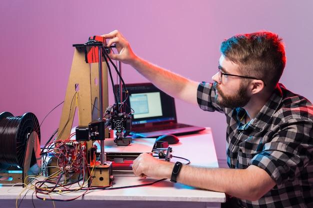 Un homme étudiant imprime un prototype sur une imprimante 3d.