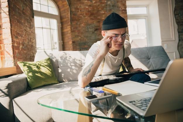 Homme étudiant à la maison pendant des cours en ligne ou des informations gratuites par lui-même