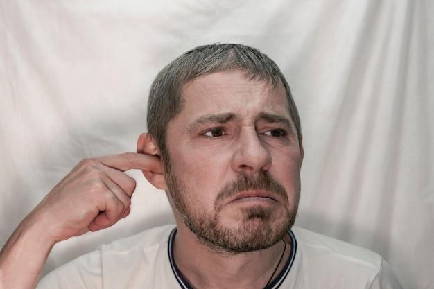 Un homme européen d'âge moyen avec une barbe choisit son oreille avec son doigt.