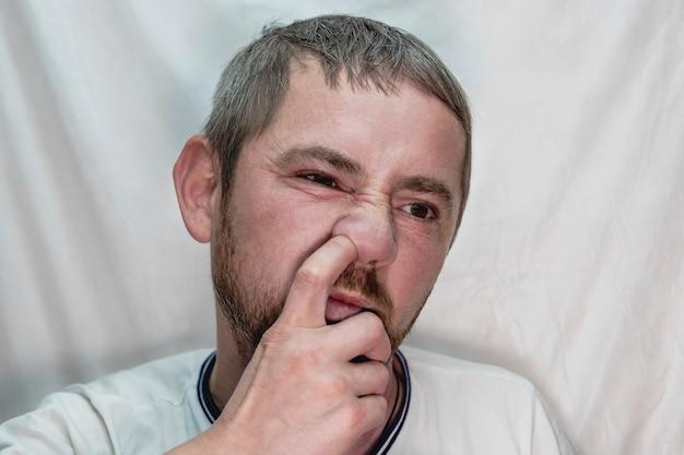 Un homme européen d'âge moyen avec une barbe se cure le nez avec un doigt.