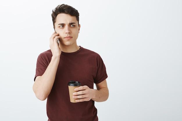 Homme européen attrayant suspect inquiet en t-shirt rouge décontracté parlant par téléphone