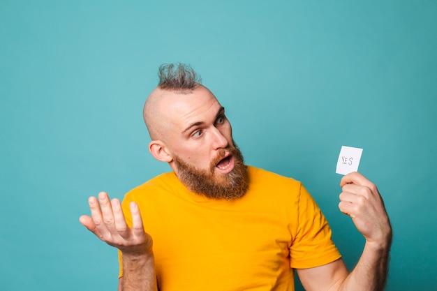 Homme européen barbu en chemise jaune isolé, tenant oui avec surprise et expression émerveillée visage excité.
