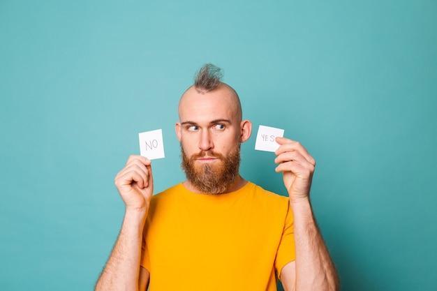 Homme européen barbu en chemise jaune isolé, tenant un rappel oui et non effrayé et choqué par la surprise et l'expression étonnée, la peur et le visage excité.