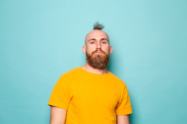 Homme européen barbu en chemise jaune isolé, visage grave brutal