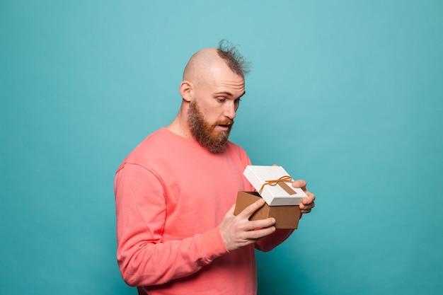 Homme européen barbu dans une boîte-cadeau d'ouverture isolé et excité pêche occasionnel