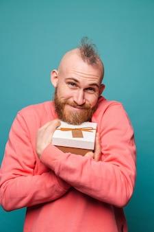 Homme européen barbu en pêche décontractée isolé, heureux étreindre boîte-cadeau