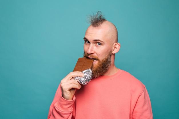 Homme européen barbu en pêche décontractée isolé, mordant le chocolat