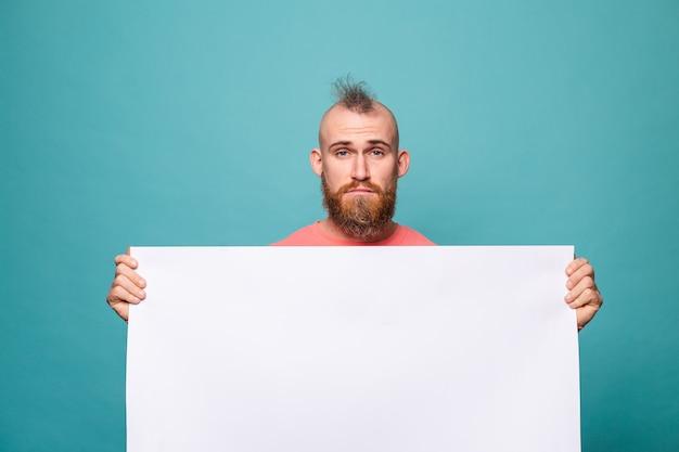 Homme européen barbu en pêche décontractée isolé, tenant un carton blanc vide avec un visage triste et malheureux