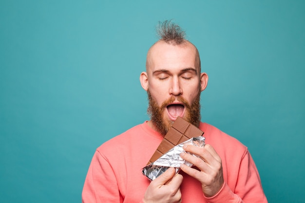 Homme européen barbu en pêche occasionnel isolé, appréciant le chocolat avec les yeux fermés morceau de morsure