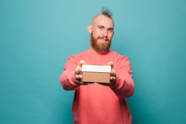 Homme européen barbu en pêche occasionnel isolé, heureux tient une boîte-cadeau