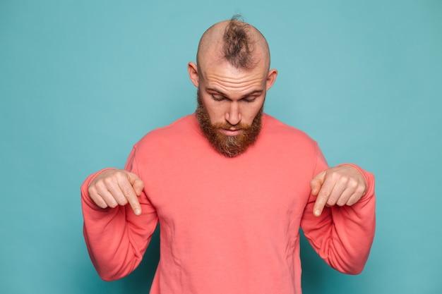 Homme européen barbu en pêche occasionnel isolé, pointant vers le bas avec les doigts montrant la publicité