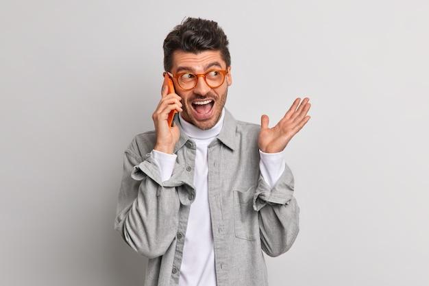 Un homme européen émotif s'exclame fort tout en parlant par téléphone portable et discute de quelque chose qui porte activement des lunettes transparentes et une chemise isolée sur un mur gris. communication technologique