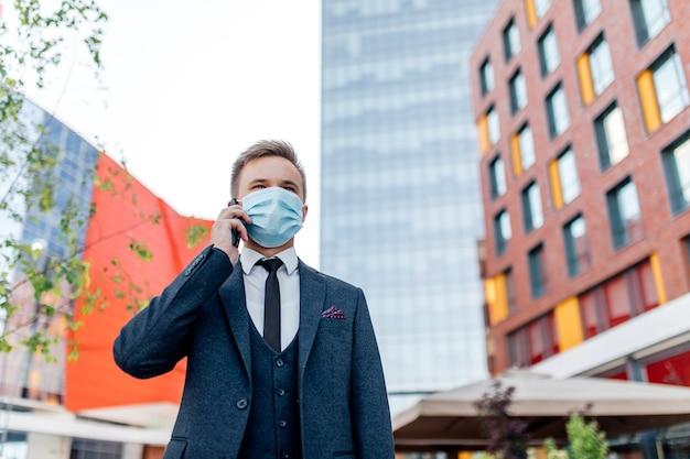 Homme européen portant un masque chirurgical à l'aide de smartphone dans la ville,