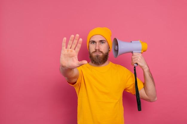 Homme européen tenir mégaphone show panneau d'arrêt sur fond rose