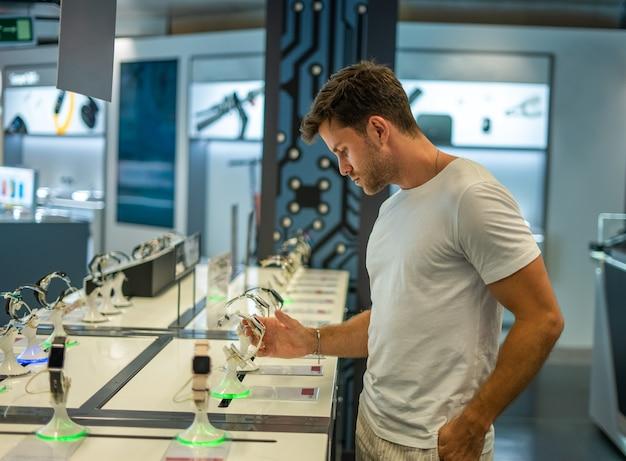 Homme examinant une vitrine avec des montres connectées en boutique