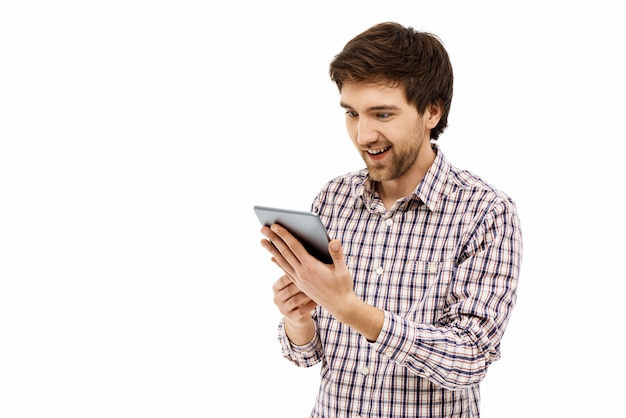Homme excité à l'aide de tablette, jouer à des jeux