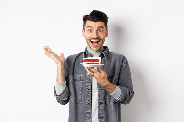 Homme excité célébrant son anniversaire, à la recherche de bonheur, tenant un gâteau avec une bougie, faisant un souhait, debout heureux sur fond blanc