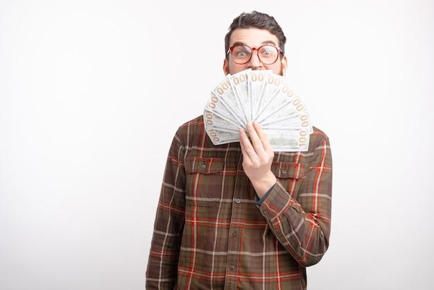 Un homme excité couvre son visage avec un ventilateur d'argent sur fond blanc.