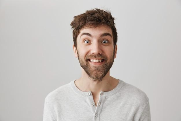 Homme excité fou avec les cheveux jetés souriant largement