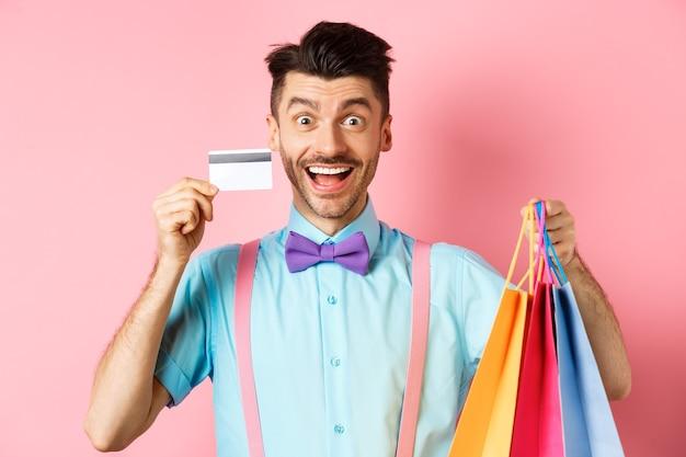 Homme excité montrant une carte de crédit en plastique et des sacs à provisions, souriant étonné lors de l'achat de cadeaux, debout sur fond rose.