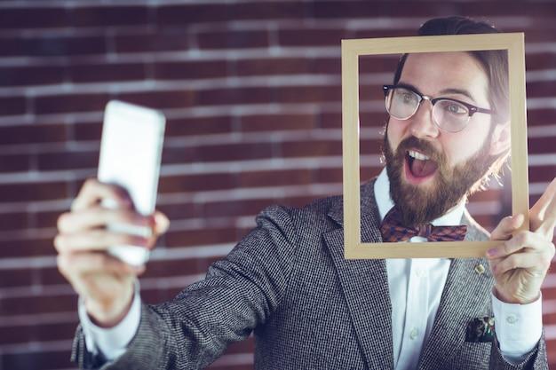 Homme excité prenant selfie tout en maintenant le cadre