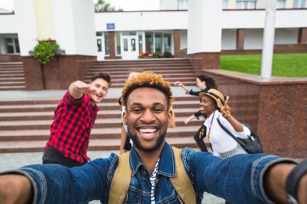 Un homme excité qui prend le selfie avec ses camarades de classe