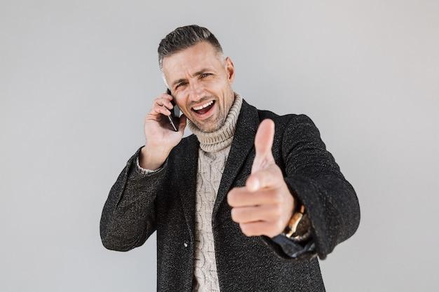 Homme excité séduisant portant un manteau debout isolé sur un mur gris, parlant au téléphone portable, pointant le doigt vers l'avant