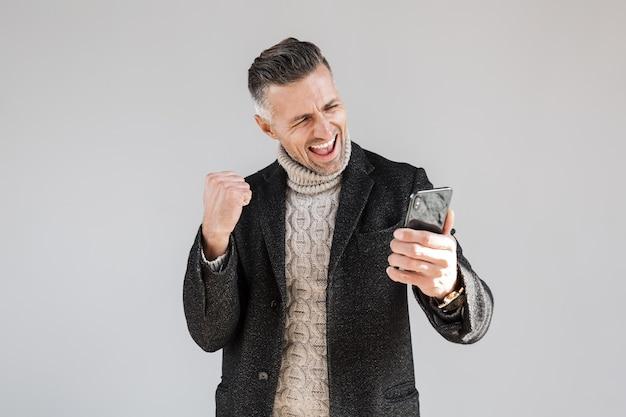 Homme excité séduisant portant un manteau debout isolé sur un mur gris, utilisant un téléphone portable, célébrant