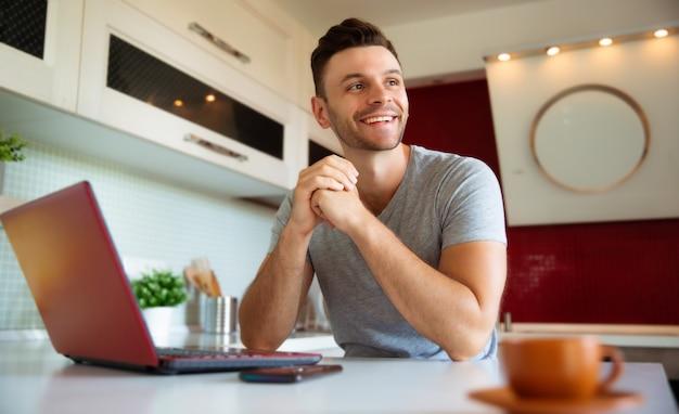 Homme excité souriant avec ordinateur portable travaillant dans la cuisine à la maison tout en détournant les yeux