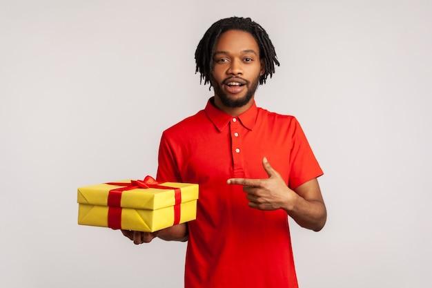 Homme excité tenant une boîte-cadeau jaune avec la bouche ouverte, pointant le doigt, regardant la caméra.