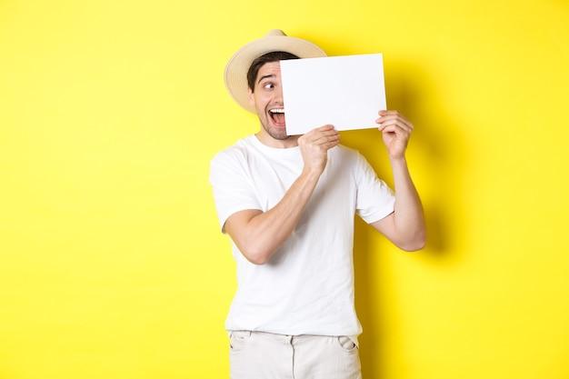 Homme excité en vacances montrant un morceau de papier vierge pour votre logo, tenant une pancarte près du visage et