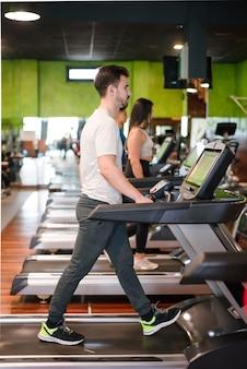 Homme exerçant cardio, entraînement en cours d'exécution sur tapis roulant au gymnase de fitness.